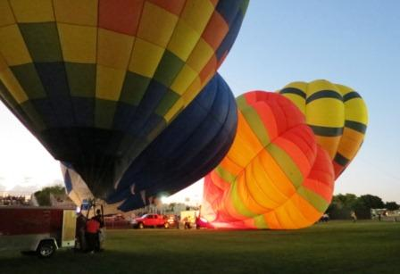 Many colorful hot air balloons are being inflated at dusk in preparation for the evening's event called Balloon Glow
